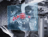 Mechanic reparing car while looking at futuristic interface — Stock Photo