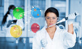 Serious chemist working with colourful dna helix diagram — Stock Photo