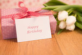 Pink wrapped present with bunch of white tulips and happy birthd — Stock Photo