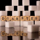 Close up on sugar cubes and dice spelling diabetes — Stock Photo