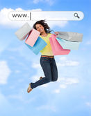 Happy girl jumping with her shopping bags under address bar — Stock Photo