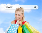 Happy blonde with her shopping bags under address bar — Stock Photo
