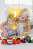 Mother and daughter chopping vegetables with yellow holographic — Stock Photo