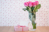Bunch of pink roses in vase with pink gift and blank card — Stock Photo