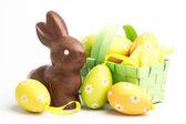 Huevos de Pascua en una cesta con conejito de chocolate — Foto de Stock