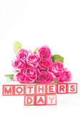 Bouquet of pink roses next to wooden blocks spelling mothers day — Stock Photo