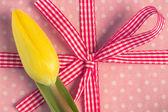Yellow tulip resting on girly present — Stock Photo