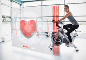 Young girl doing exercise bike with futuristic interface — Foto Stock