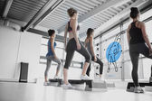 Rear view of women doing exercise with blue futuristic interface — Stok fotoğraf