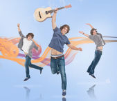Three of the same young man jumping for joy — Stock Photo