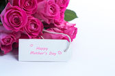 Bouquet of beautiful roses with happy mothers day card on a tabl — Stock Photo