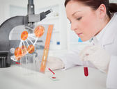 Scientist pouring drop of blood onto glass with futuristic inter — Stock Photo