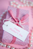 Pink gift wrapped box with mothers day greeting and pearls — Stock Photo