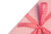 Pink gift wrapped present with gingham ribbon — Stock Photo