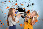 Girl shouting at another covering her ears through megaphone — Stock Photo