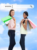 Happy girls with their shopping bags under address bar — Stock Photo