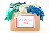 Cardboard donation box with clothes on white background — Stock Photo