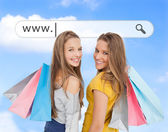 Smiling girls with their shopping bags under address bar — Stock Photo