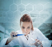 Scientist pouring liquid into erlenmeyer with futuristic screen — Stock Photo