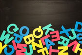 Alphabet magnets in a jumble on blackboard — Stock Photo