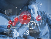 Mechanic reparing car while consulting futuristic interface — Stok fotoğraf