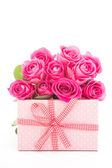 Bouquet of beautiful pink roses next to a pink gift on white bac — Stock Photo