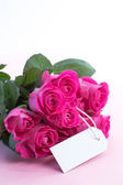Bouquet of pink roses with an empty card on a table — Stock Photo