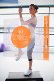 Woman doing exercise with futuristic interface showing calories — Stock Photo