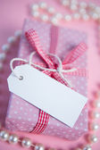 Pink gift wrapped box with blank tag and pearls — Stock Photo