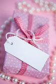 Rosa regalo envuelto caja con la etiqueta en blanco y perlas — Foto de Stock