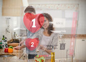 Happy couple making dinner using interface instructions — Stock Photo