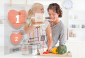 Cute couple making dinner using interface instructions — Stock Photo
