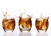 Serial arrangement of whiskey splashing in tumbler — Stock Photo