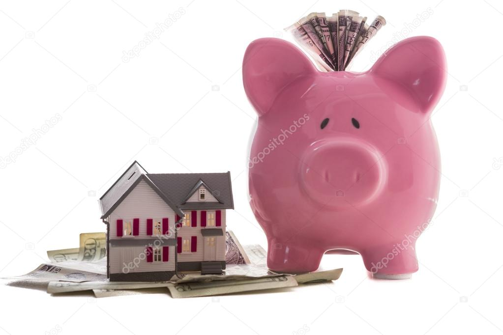 Фотообои Close up of a pink piggy bank with dollars beside miniature hous