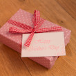 Pink wrapped present with mothers day card — Stock Photo