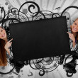 Girls pointing to black copy space with artistic swirl frame - Stockfoto