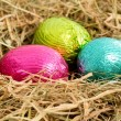 Three colouful easter eggs nestled in straw nest — Stockfoto