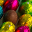 Colourful easter eggs with one unwrapped - Stock Photo