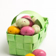 Speckled colourful easter eggs in a green wicker basket - Stock Photo