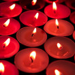 Stock Photo: Red candles lighting up dark