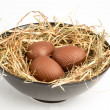 Chocolate easter eggs in straw in bowl — Stock Photo