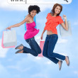 Happy girls jumping with their shopping bags under address bar — Stock Photo #24150287