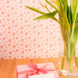 Stock Photo: Pink wrapped present with blank card beside vase of tulips