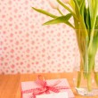 Pink wrapped present with blank card beside vase of tulips — Stock Photo