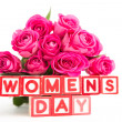 Bouquet of pink roses next to wooden blocks spelling womens day — Stock Photo #24150401