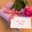 Pink wrapped present with mothers day card and pink rose — Stock Photo