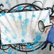 Young man shouting through megaphone with blue paint - Stockfoto