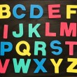 Alphabet magnets stuck on blackboard — Stock Photo