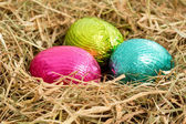 Three colouful easter eggs nestled in straw nest — Stock Photo