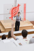 Teacher in front of futuristic interface pointing college studen — Stock Photo